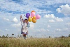 Muchacha feliz con los globos coloridos Foto de archivo libre de regalías