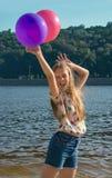 Muchacha feliz con los globos coloridos en la playa Imagenes de archivo