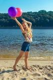 Muchacha feliz con los globos coloridos en la playa Foto de archivo