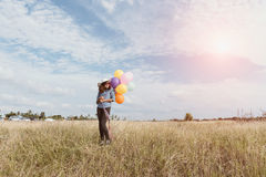 Muchacha feliz con los globos coloridos, en los prados fotografía de archivo libre de regalías