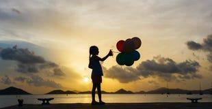 Muchacha feliz con los globos en la puesta del sol Fotos de archivo libres de regalías