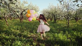 Muchacha feliz con los globos que corren en el jardín floreciente almacen de video