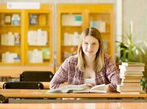 Muchacha feliz con los libros en la biblioteca Fotografía de archivo libre de regalías