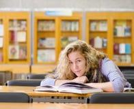 Muchacha feliz con los libros en la biblioteca mirada de la cámara Fotografía de archivo