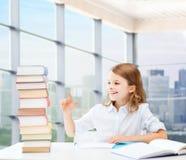 Muchacha feliz con los libros y el cuaderno en la escuela Imagen de archivo libre de regalías