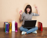 Muchacha feliz con los panieres que se sientan en el piso con el ordenador portátil a Imagen de archivo libre de regalías