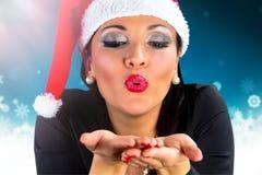 Muchacha feliz con nieve que sopla del sombrero de Santa Claus Imagen de archivo libre de regalías