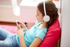 Muchacha feliz con smartphone y los auriculares en casa Fotos de archivo libres de regalías