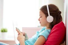 Muchacha feliz con smartphone y los auriculares en casa Fotografía de archivo