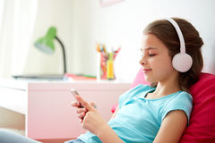 Muchacha feliz con smartphone y los auriculares en casa Imágenes de archivo libres de regalías