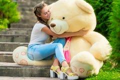 Muchacha feliz con un oso de peluche enorme en el parque Fotografía de archivo