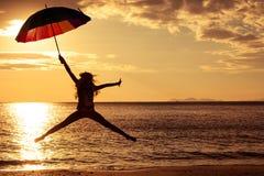 Muchacha feliz con un paraguas que salta en la playa Fotografía de archivo