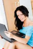 Muchacha feliz con una computadora portátil en el país Foto de archivo