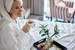 Muchacha feliz con una taza de café Albornoz que lleva y toalla del estilo de la mujer casera de la relajación después de la duch fotos de archivo libres de regalías
