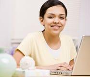 Muchacha feliz, confidente con las paréntesis usando la computadora portátil Imagen de archivo libre de regalías