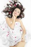Muchacha feliz cubierta con la hoja de cama en flores Fotografía de archivo