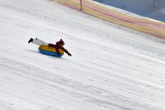 Muchacha feliz cuesta abajo en el tubo de la nieve en estación de esquí Fotografía de archivo libre de regalías