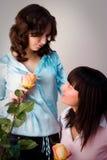 Muchacha feliz de dos amigos con las rosas amarillas Fotografía de archivo