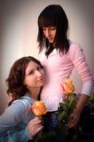 Muchacha feliz de dos amigos con las rosas amarillas Imágenes de archivo libres de regalías