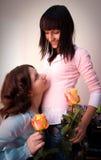 Muchacha feliz de dos amigos con las rosas amarillas Imagen de archivo libre de regalías