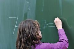 Muchacha feliz de la escuela en clases de la matemáticas Foto de archivo