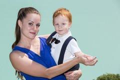 Muchacha feliz de la mamá y del niño que abraza en la naturaleza el concepto de niñez y de familia Imagenes de archivo