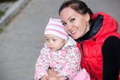 Muchacha feliz de la mamá y del niño que abraza en la naturaleza el concepto de niñez y de familia Fotos de archivo