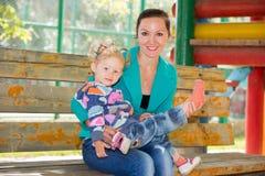 Muchacha feliz de la mamá y del niño que abraza en la naturaleza el concepto de niñez y de familia Imágenes de archivo libres de regalías