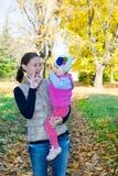 Muchacha feliz de la mamá y del niño que abraza en la naturaleza en la caída El concepto de niñez y de familia Imagen de archivo libre de regalías