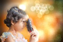 Muchacha feliz de la moda que juega con el cepillo de pelo Foto de archivo