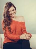 Muchacha feliz de la mujer que se sienta en el sofá en casa Foto de archivo libre de regalías