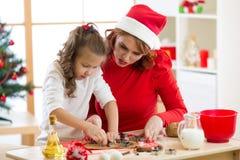 Muchacha feliz de la mujer y del niño que corta las galletas de la Navidad fuera de la pasta juntas Foto de archivo libre de regalías