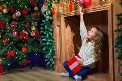 Muchacha feliz de la Feliz Navidad con el regalo mágico en casa cerca de Christma Imagen de archivo