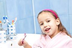 Muchacha feliz de la sonrisa adentro él cuarto de baño, lavándose el diente Foto de archivo libre de regalías