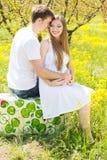 Muchacha feliz de los pares con el novio en jardín de flores Fotos de archivo libres de regalías