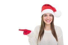 Muchacha feliz de Papá Noel que señala a la izquierda Imágenes de archivo libres de regalías
