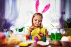 Muchacha feliz de pascua en los oídos del conejito que pintan los huevos, pequeño niño en casa Día de fiesta de la primavera fotografía de archivo