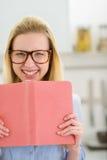Muchacha feliz del adolescente con el libro en cocina Fotos de archivo