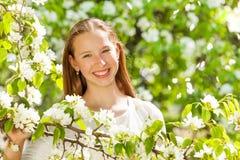 Muchacha feliz del adolescente con las flores blancas en árbol Imagenes de archivo