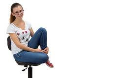 Muchacha feliz del adolescente con los vidrios que se sientan en silla Imagenes de archivo