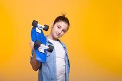 Muchacha feliz del adolescente con su monopatín azul en hombros Imagen de archivo