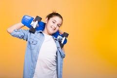 Muchacha feliz del adolescente con su monopatín azul en hombros Fotografía de archivo