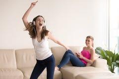 Muchacha feliz del adolescente dos que disfruta de música en casa Imagen de archivo
