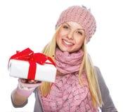 Muchacha feliz del adolescente en el sombrero del invierno que da presentando la caja Imágenes de archivo libres de regalías