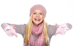 Muchacha feliz del adolescente en sombrero y bufanda del invierno que señala abajo Fotografía de archivo libre de regalías