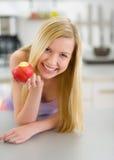 Muchacha feliz del adolescente que come la manzana en cocina Fotografía de archivo