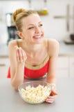 Muchacha feliz del adolescente que come las palomitas en cocina Fotografía de archivo libre de regalías