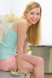 Muchacha feliz del adolescente que desayuna en cocina Imagenes de archivo