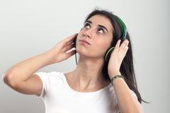Muchacha feliz del adolescente que escucha la música aislada en un b blanco Foto de archivo