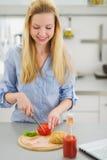 Muchacha feliz del adolescente que hace el bocadillo en cocina Fotos de archivo